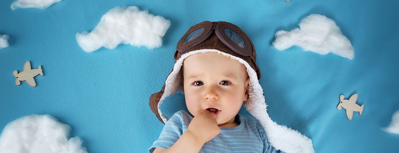 Baby in front of cloud background wearing pilot goggles